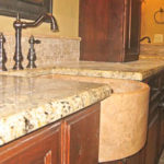 Curved apron-front undermount sink in a granite kitchen countertop