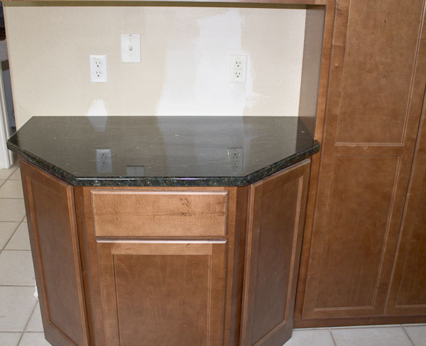 Peacock green granite kitchen round rock texas for Angled kitchen cabinets